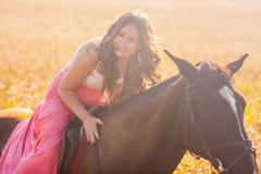 ragazza sorridente a cavallo in vestito fotografia stock libera da diritti