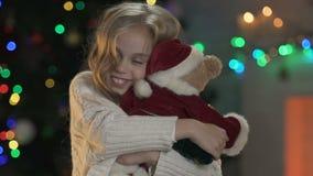 Ragazza sorridente che abbraccia strettamente le feste aspettanti ed i regali di Natale dell'orso della peluche video d archivio