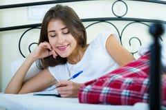 Ragazza sorridente che fa la lista di acquisto in camera da letto Immagine Stock Libera da Diritti