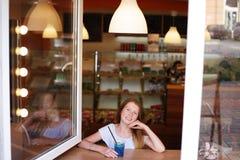 Ragazza sorridente che guarda dalla finestra nad del caffè che beve bevanda blu Immagini Stock