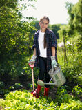 Ragazza sorridente che lavora al giardino con la pala e l'annaffiatoio fotografie stock