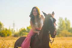 ragazza sorridente che monta un cavallo in un rosa fotografia stock