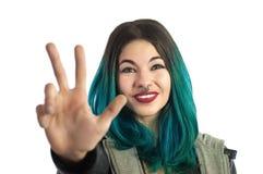 Ragazza sorridente che mostra le tre dita, contanti il segno della mano Immagine Stock