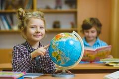 Ragazza sorridente che mostra sul globo all'aula della scuola Concetto della scuola ed educativo Fotografia Stock