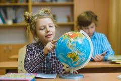 Ragazza sorridente che mostra sul globo all'aula della scuola Concetto della scuola ed educativo Immagine Stock
