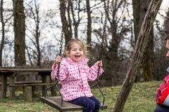 Ragazza sorridente che oscilla con suo padre Immagine Stock Libera da Diritti