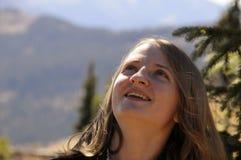 Ragazza sorridente che osserva in su sulla vetta Fotografia Stock Libera da Diritti