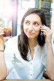 Ragazza sorridente che parla sul telefono e sul bere un cocktail Fotografia Stock Libera da Diritti