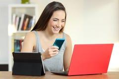 Ragazza sorridente che per mezzo dei dispositivi multipli a casa immagini stock libere da diritti