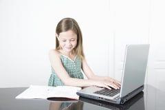 Ragazza sorridente che per mezzo del computer portatile Fotografia Stock