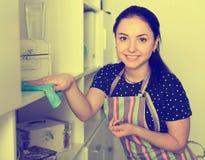 Ragazza sorridente che pulisce polvere sugli scaffali Immagini Stock Libere da Diritti