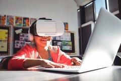 Ragazza sorridente che scrive sul computer portatile mentre usando le cuffie ed i vetri di realtà virtuale Fotografia Stock Libera da Diritti