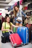 Ragazza sorridente che seleziona valigia Immagine Stock