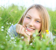 Ragazza sorridente che si distende all'aperto Fotografia Stock