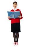Ragazza sorridente che si leva in piedi con il libro di esercitazione Fotografie Stock