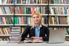 Ragazza sorridente che si siede ad uno scrittorio nella biblioteca che lavora con Immagini Stock