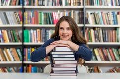 Ragazza sorridente che si siede ad uno scrittorio nella biblioteca con il suo braccio Immagine Stock