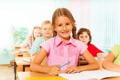 Ragazza sorridente che si siede allo scrittorio in aula Immagine Stock