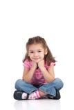 Ragazza sorridente che si siede con i piedini attraversati Fotografia Stock