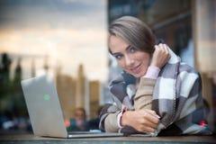 Ragazza sorridente che si siede con il computer portatile in caffè Fotografie Stock Libere da Diritti