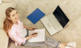 Ragazza sorridente che si siede sul pavimento a casa che studia, Fotografia Stock