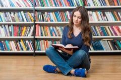 Ragazza sorridente che si siede sul pavimento nella lettura delle biblioteche Fotografie Stock