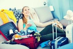 Ragazza sorridente che si siede sul sofà e sulla valigia d'imballaggio Immagini Stock