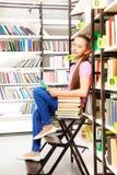 Ragazza sorridente che si siede sulla scala a libretto in biblioteca Fotografia Stock