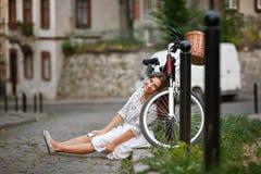 Ragazza sorridente che si siede sulla strada vicino alla bicicletta Fotografia Stock Libera da Diritti