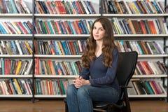 Ragazza sorridente che si siede in una poltrona nella biblioteca con la h Fotografie Stock