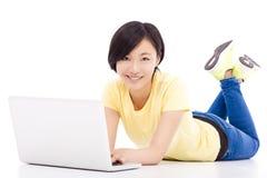 Ragazza sorridente che si trova sul pavimento con un computer portatile Immagine Stock