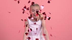 Ragazza sorridente che soffia i coriandoli in forma di cuore dalle mani, fest di giorno di biglietti di S. Valentino del san stock footage