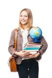 Ragazza sorridente che sta con la borsa, i libri ed il globo Fotografia Stock