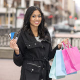 Ragazza sorridente che tiene una carta di credito ed i sacchetti della spesa. Fotografia Stock