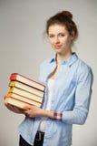 Ragazza sorridente che tiene una pila di libri Immagine Stock