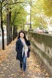 Ragazza sorridente cinese che cammina sulla via di autunno con le foglie cadute Immagini Stock