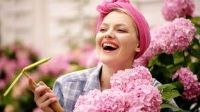 Ragazza sorridente con i grandi germogli dei fiori rosa giardiniere felice della donna con i fiori Cura ed innaffiatura del fiore archivi video