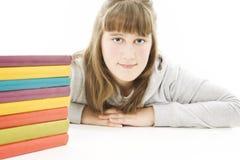 Ragazza sorridente con i libri di banco sulla tabella. Fotografia Stock Libera da Diritti
