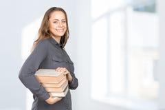 Ragazza sorridente con i libri impilati Immagine Stock