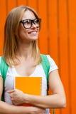 Ragazza sorridente con i libri in mezzo della parete arancio Fotografia Stock Libera da Diritti