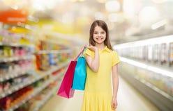 Ragazza sorridente con i sacchetti della spesa sopra il supermercato Fotografia Stock Libera da Diritti