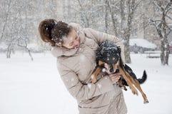 Ragazza sorridente con il cane nella neve di inverno Immagine Stock
