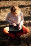 Ragazza sorridente con il computer portatile all'aperto Fotografia Stock Libera da Diritti