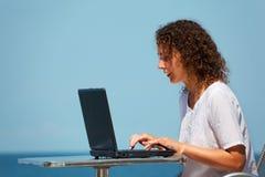 Ragazza sorridente con il computer portatile. Si siede alla tabella sulla spiaggia fotografie stock libere da diritti