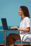 Ragazza sorridente con il computer portatile. Si siede alla tabella sulla spiaggia Fotografia Stock