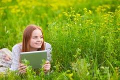 Ragazza sorridente con il computer portatile su erba Fotografia Stock Libera da Diritti