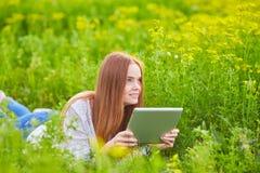 Ragazza sorridente con il computer portatile su erba Immagine Stock Libera da Diritti