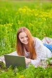Ragazza sorridente con il computer portatile su erba Immagine Stock