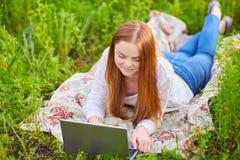 Ragazza sorridente con il computer portatile su erba Immagini Stock