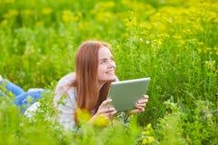 Ragazza sorridente con il computer portatile su erba Fotografie Stock Libere da Diritti